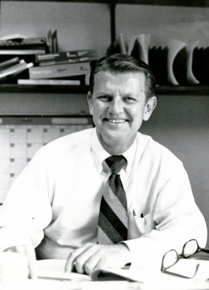 Dr. Norm Tully sitting at desk in the 1980s.