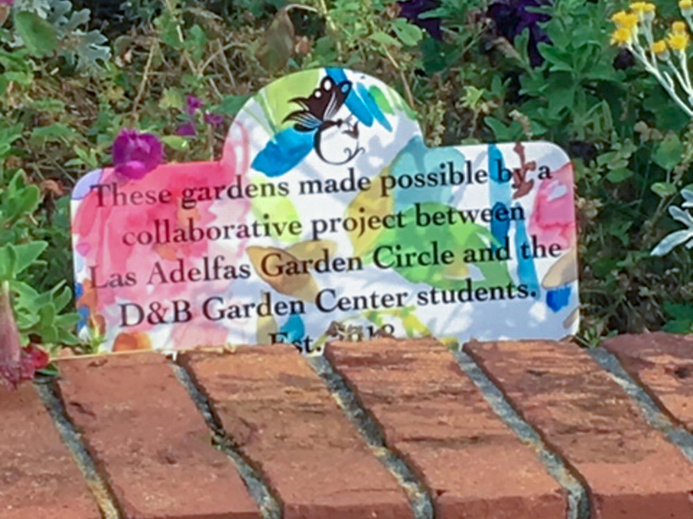 Sign in garden that reads–These gardens made possible by collaborative project between Las Adelfas Garden Circle and the D&B Garden Center students.