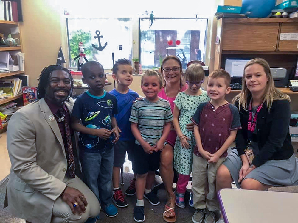Dr. Dré poses for photo with a Blind Elementary class.