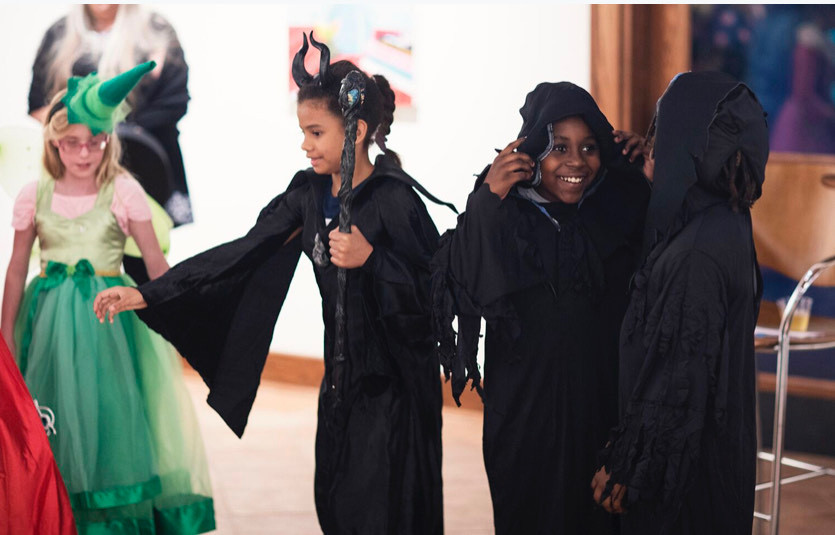 Blind student dressed as Maleficent holding a staff and another boy dressed as one of her minions.