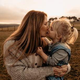 Mother and daughter sharing a kiss