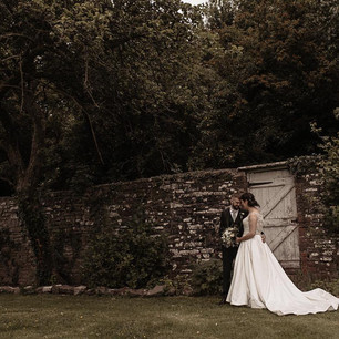 Distance shot of bride and groom walking by stone wall with trees overhanging