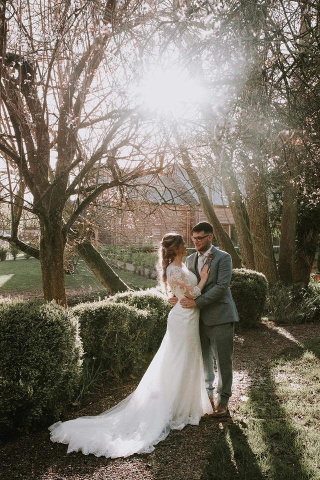 bride and groom embracing amidst forest wooded backdrop.jpg