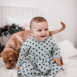 Baby on bed with dog behind her