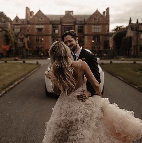 Bride and groom embracing with manor home in background.jpg
