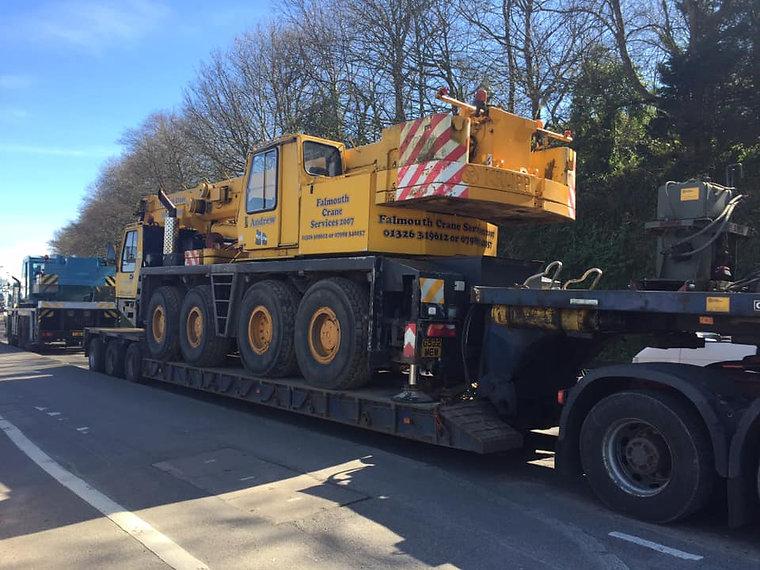 Lorry carrying yellow crane vehicle.jpg