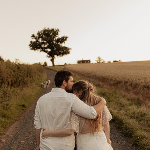 Rear shot of couple embracing on country track at sunset