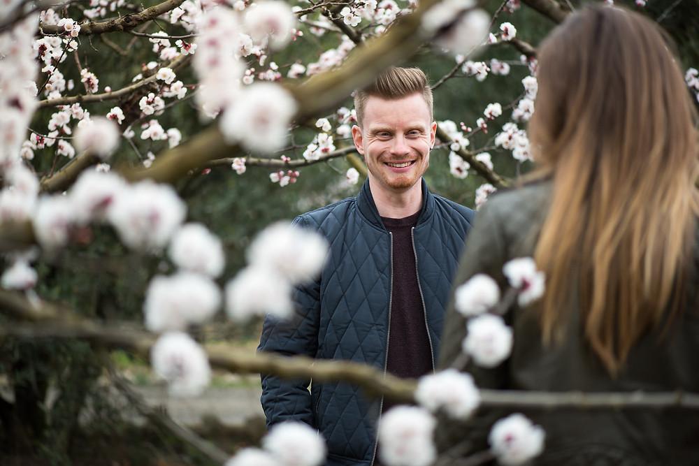 Séance photo Couple dans un champ d'abricotier en fleur au printemps