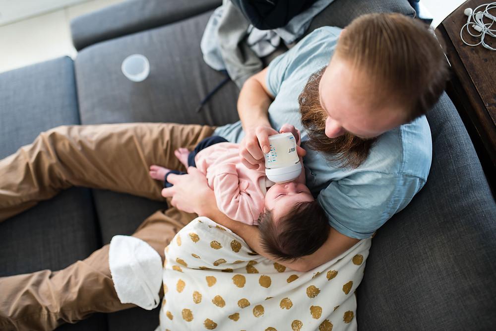 papa donne le biberon a son enfant à la maison