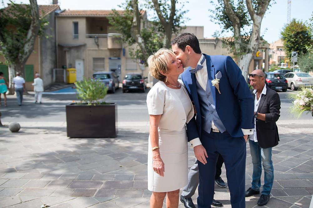 le futur marié embrassant sa maman devant la mairie