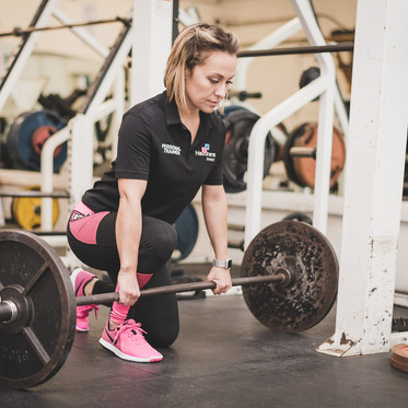 Lifestyle personal branding portait of a female personal fitness trainer lifting weights in gym
