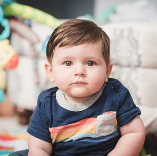 Lifestyle child portrait of newborn boy sitting up in the family home
