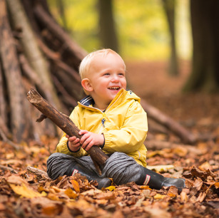 Lifestyle child portrait of young boy outdoors in the woods in autumn
