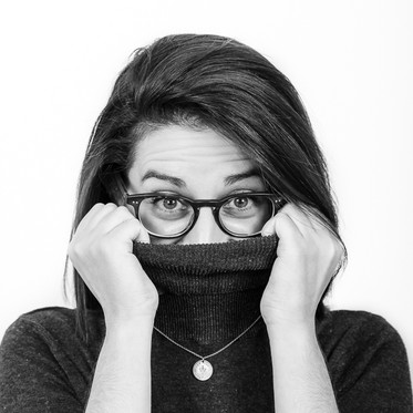 Black and white personal branding studio portrait of a female pulling jumper over her mouth