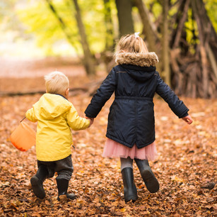 Lifestyle child portrait of sister and brother holding hands outdoors in the woods in autumn