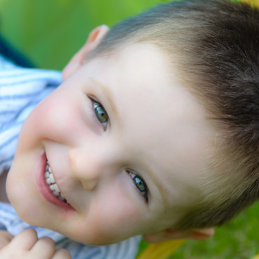 Lifestyle child portrait of young boy lying in grass in garden of amily home