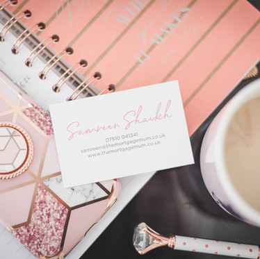 Personal branding flatlay photograph of a business card, mobile phone, pen, notepad and cup of coffee