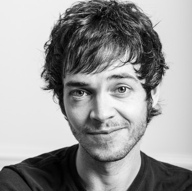 Black and white personal branding portrait of a male against a studio background