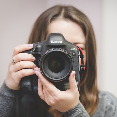 Personal branding portrait of a female photographer holding a camera to their eye