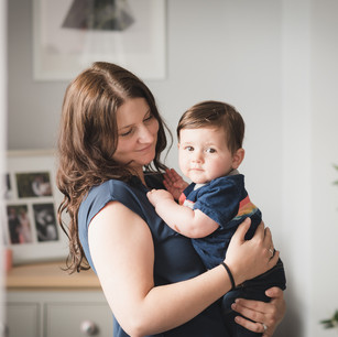 Lifestyle family portrait of mother holding newborn son in living room