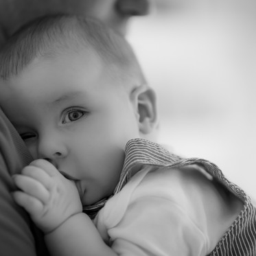 Black and white lifestyle child portrait of father holding newborn boy in the family home