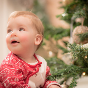 Lifestyle child portrait of newborn boy in the family home next to Christmas tree