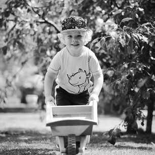 Black and white lifestyle child portrait of young boy with wheelbarrow in the family garden