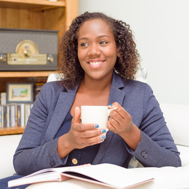 Lifestyle personal branding portrait of a female professional in the living room holding a coffee cup