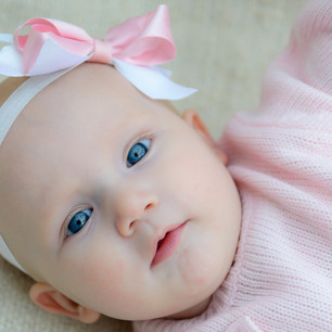 Lifestyle child portrait of newborn girl with pink bow lying on back in family home