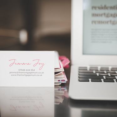 Personal branding product photograph of a business card on a table next to a laptop