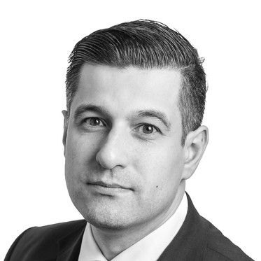 Black and white corporate portrait of a male lawyer against a white background