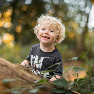 Lifestyle child portrait of young boy outdoors in the woods