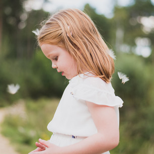 Lifestyle child portrait of young girl outdoors looking at flowers