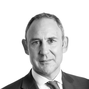 Black and white corporate portrait of a male professional against a white background