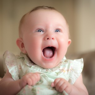 Lifestyle child portrait of newborn girl laughing in the family home