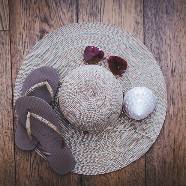 Personal branding product flatlay of a sun hat, flip-flops and sunglasses