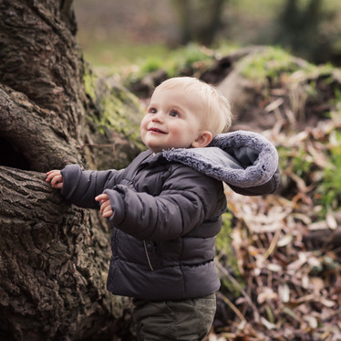 Lifestyle child portrait of young boy outdoors in the woods next to a tree
