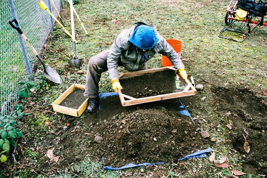 Archaeologist screening UXO excavation backdirt for artifacts