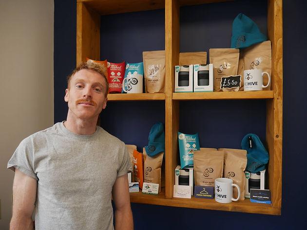 Man stood by a shelf with coffee