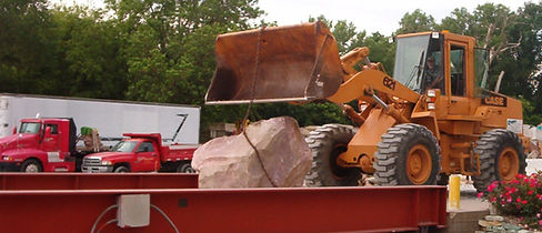 Payloader lifting large Dakota Pink boulder onto scale