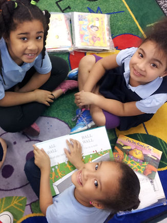 3 WHA Students reading books in class.