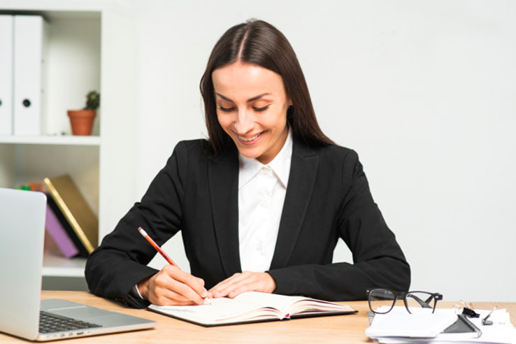 smiling-young-woman-writing-diary-with-p