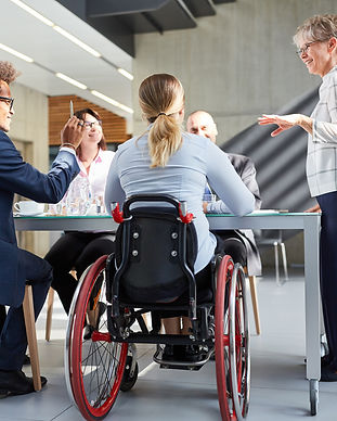 Business meeting with 5 people around a table - one person is in a wheelchair