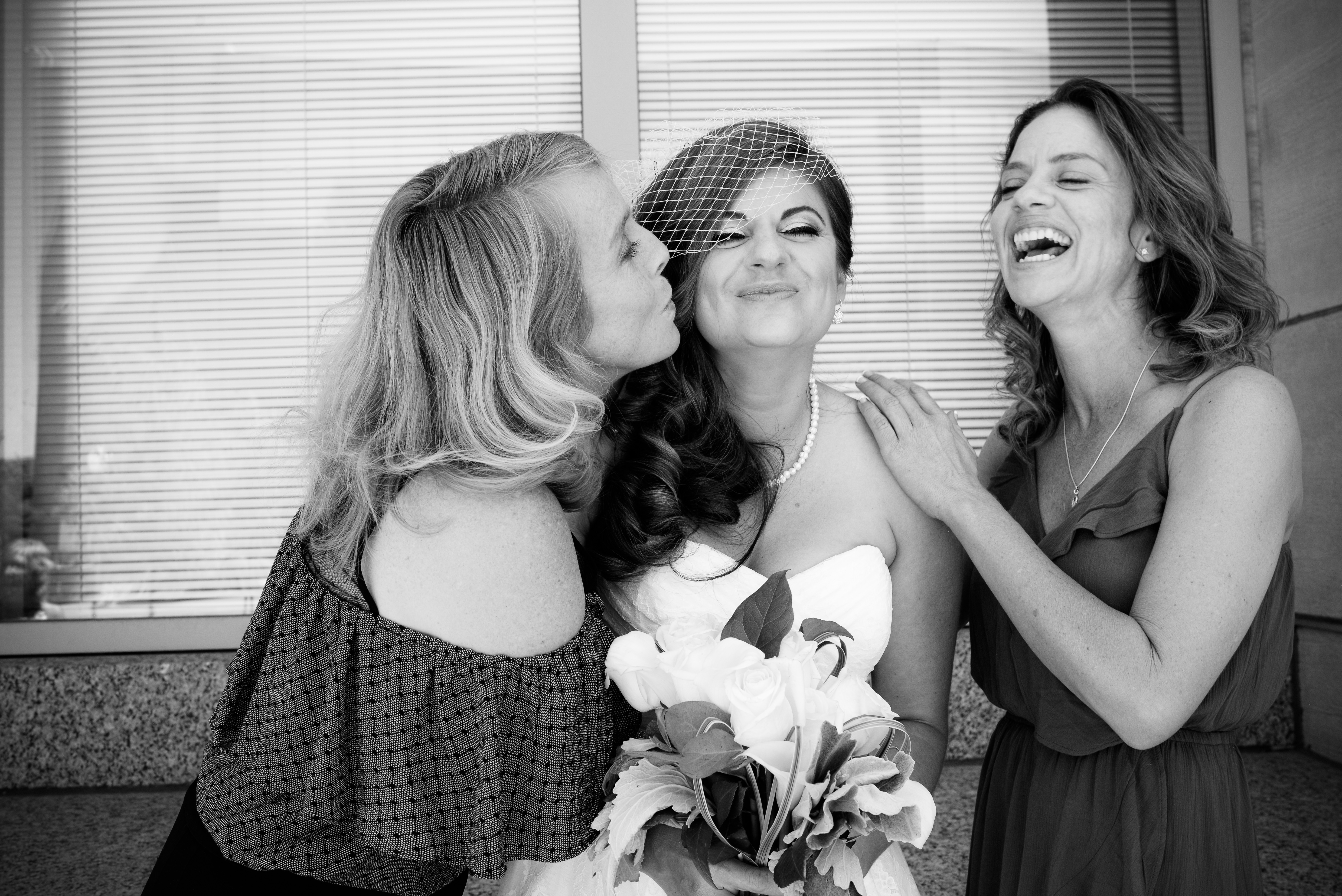Sisters of bride laughing with her