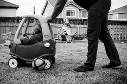 Dad pushing toddler in car