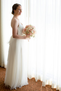 Bride standing with white curtain