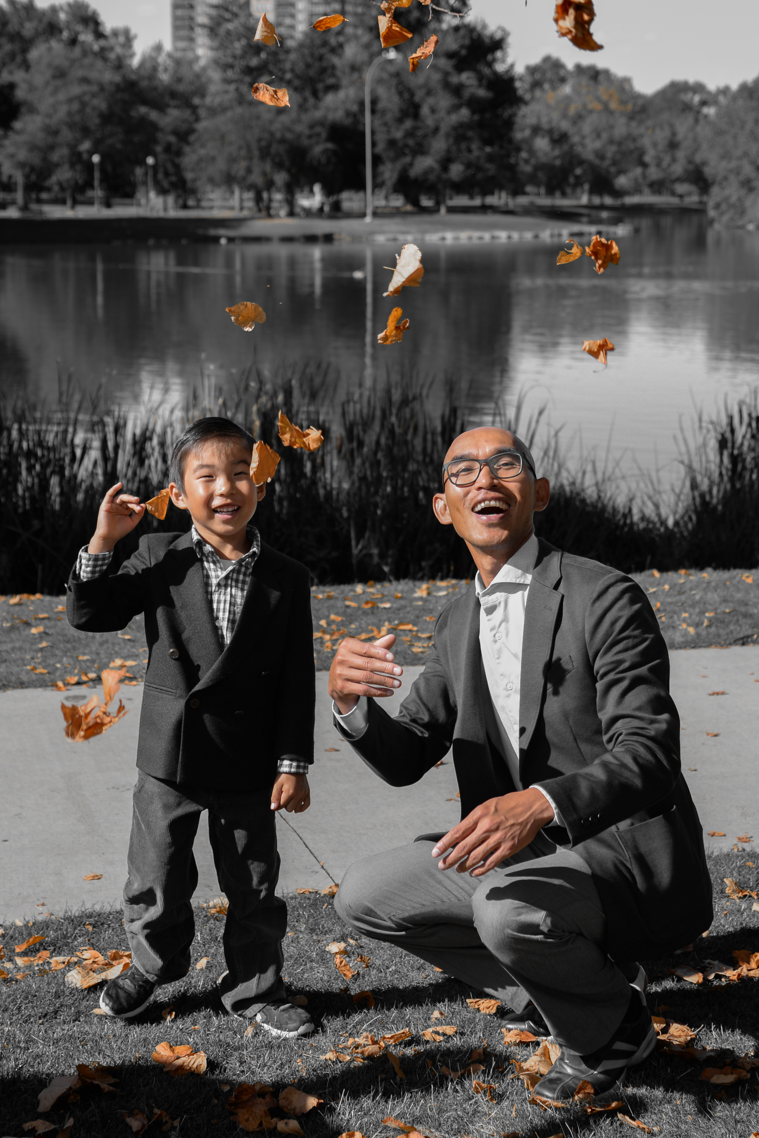 Boy and dad throw fall leaves