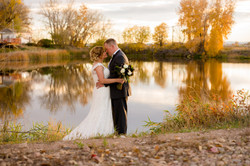 Bride and groom with lake in fall