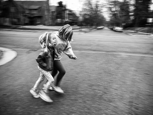 Sisters running across street
