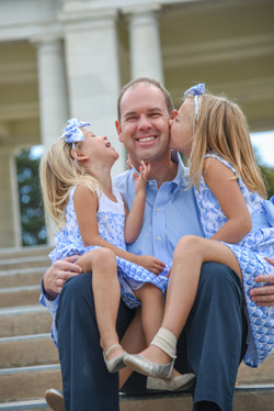 Daughters kissing dad on steps